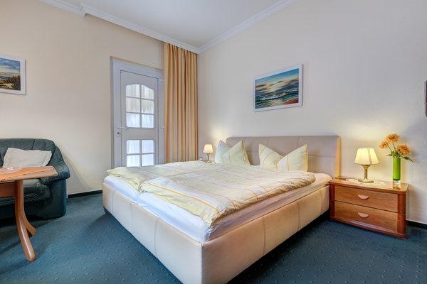 kombiniertes Wohn-/Schlafzimmer mit Doppelbett und Zugang auf die Terrasse
