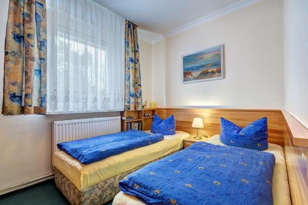 Schlafzimmer mit 2 Einzelbetten. Fenster mit Rollladen.