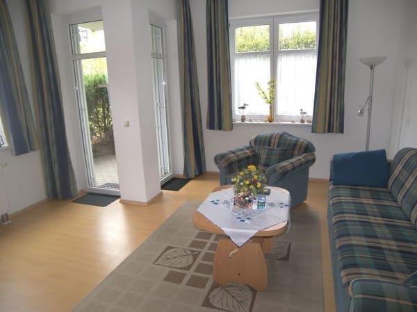 Das gemütliche Wohnzimmer mit ausziebarer Couch und Ausgang zur Terrasse.