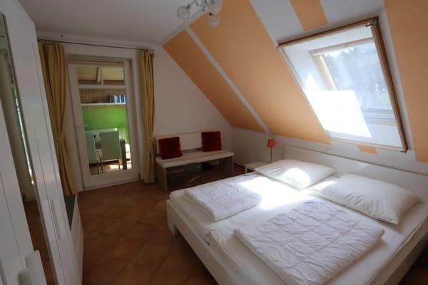 1. Schlafzimmer mit Doppelbett und Terrassentür, Sitzecke mit Tisch