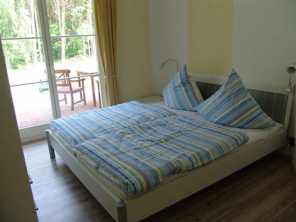2. Schlafzimmer und Doppelbett mit Terrassentür in den Garten
