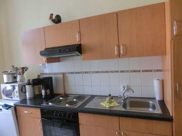 Küche mit Herd und Backofen, Geschirrspüler, Mikrowelle, Wasserkocher und Kaffeemaschine sowie vielen Küchenutensilien