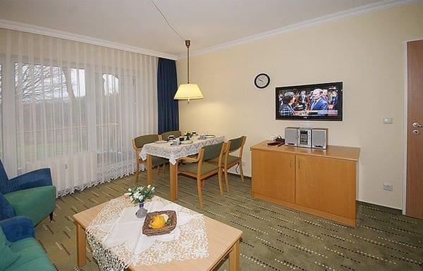 Wohnzimmer mit Schlafcouch und Flat-TV