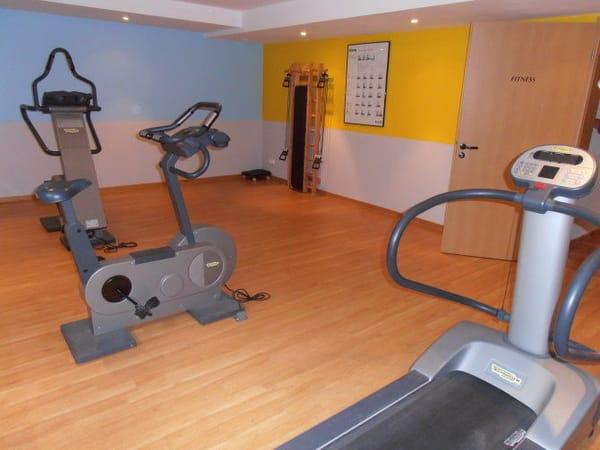 Fitnessraum mit Stepper, Laufband, Fahrrad und Sprossenwand
