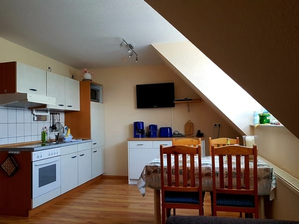 Voll ausgestattete Küche mit Kühlschrank & Kühlfach, Backofen, Ceranfeld, Mikrowelle, Kaffeemaschine, Toaster und Wasserkocher.