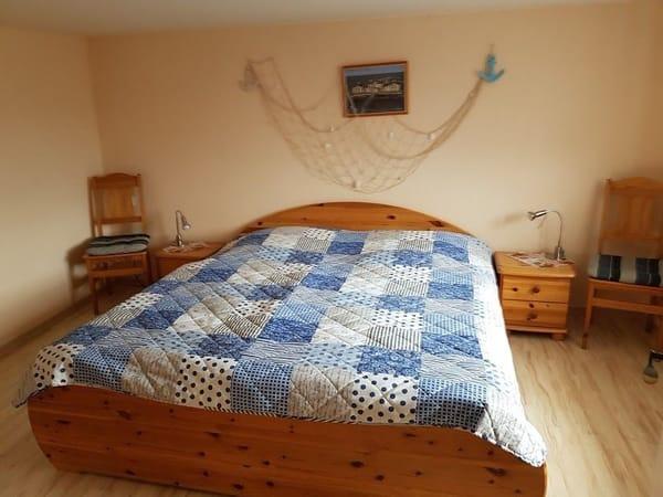 Schlafzimmer mit Doppelbett und großem Kleiderschrank.