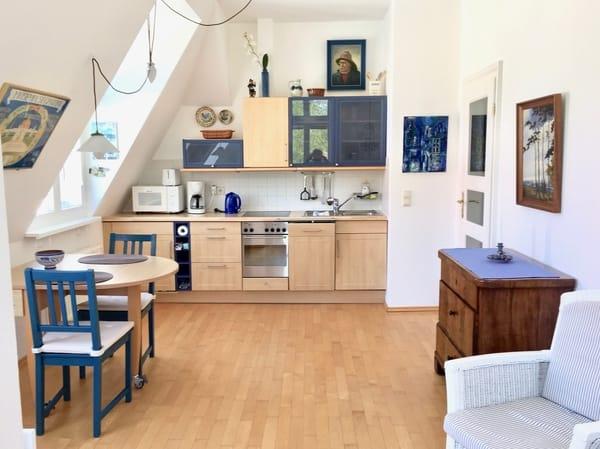 Küchenzeile mit Backofen und Geschirrspüler. Aus dem Fenster kann man die Seebrücke sehen.