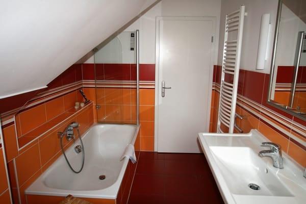 Badezimmer mit Wanne und Duschabtrennung