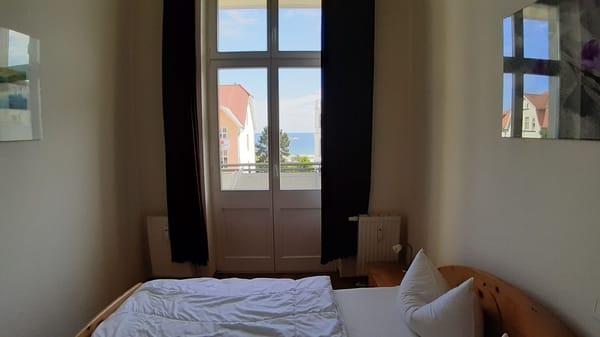 großes Schlafzimmer mit Zugang zum Balkon und Aussicht