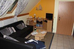 Wohnzimmer mit Sitzecke und Flat-TV