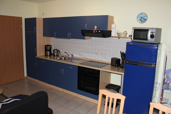 Küchenzeile mit Herd, Kühlschrank, Kaffeemaschine, Wasserkocher, Toaster.