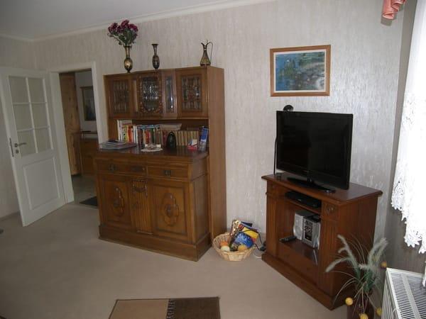 Wohnzimmer mit antikem Schrank.