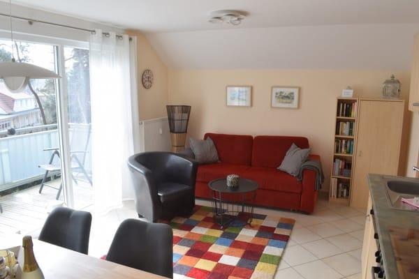 Das Wohnzimmer mit großer Fensterfront in Südostausrichtung ist mit einer hochwertigen Couch mit Relax- und Schlaffunktion ausgestattet.