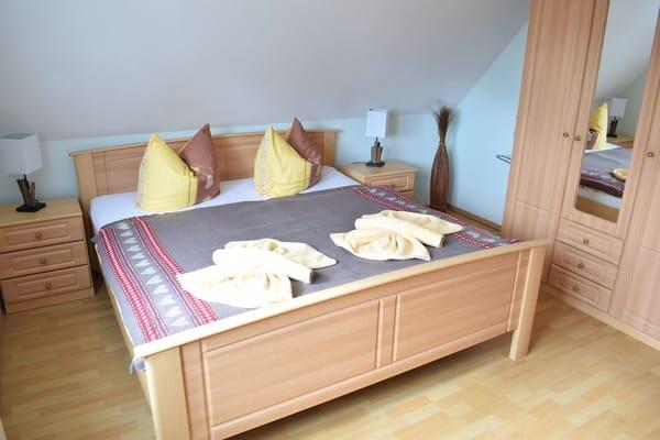 Das geräumige Schlafzimmer bietet ausreichend Platz für ein zusätzliches Kinderbett.