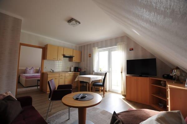 Wohnzimmer mit Balkon und Wohnküche