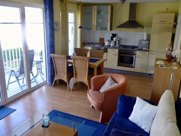 Wohnzimmer mit offener Küche und Zugang zum Balkon I