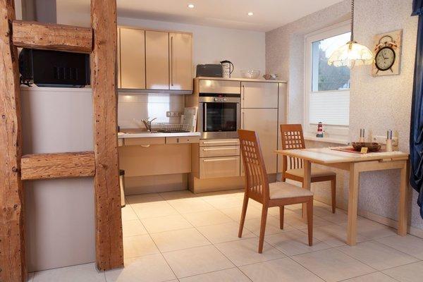 Zum Wohnzimmer offene Küche. Ceranfeld-Herd, Spülmasachine, Kühlschrank mit Gefrierfach, Umluftherd, Mikrowelle.