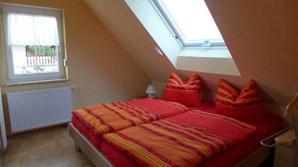 Blick ins kleinere Schlafzimmer. Das Dachflächenfenster ist mit einer Außenjalousie versehen.
