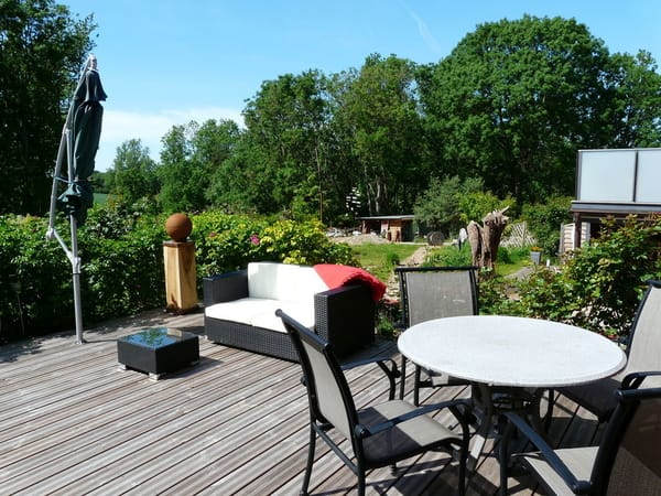 Große Terrasse gartenseitig mit Bestuhlung, Lounge-Möbel, Grill, Sonnenliege und Sonnenschirm
