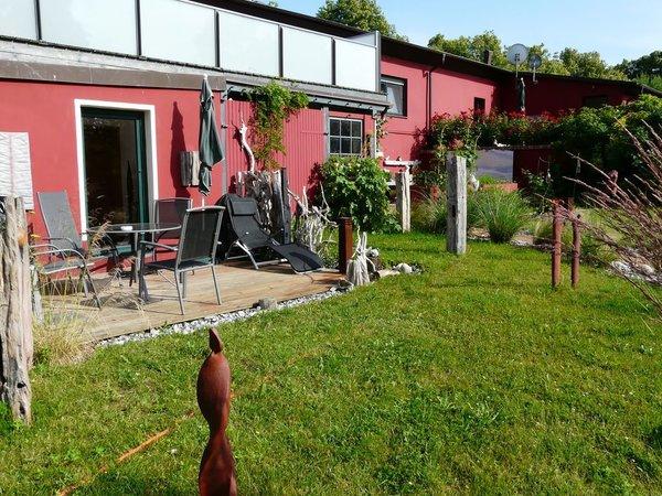 Terrase mit Bestuhlung, Grill, Sonnenschirm und Liegewiese neben der Terrasse