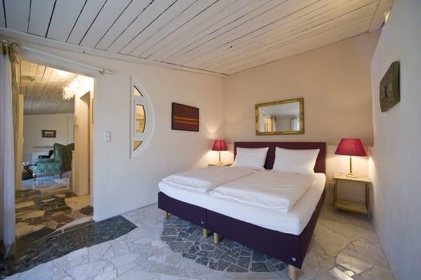 Schlafzimmer mit Komfort-Hotelboxspringbett (1,80 m x 2,00 m, Bandscheiben-Federkernmatratze), mit Blick in den Garten