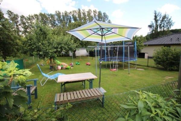 Spielplatz bestehend aus Trampolin, Sandkasten, Schaukeln, Rutschen für große und kleine Kinder