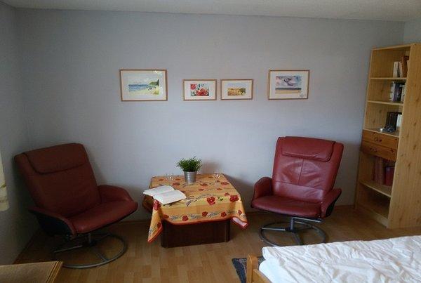 Wohn-/Schlafzimmer mit Sitzgelegenheit und TV