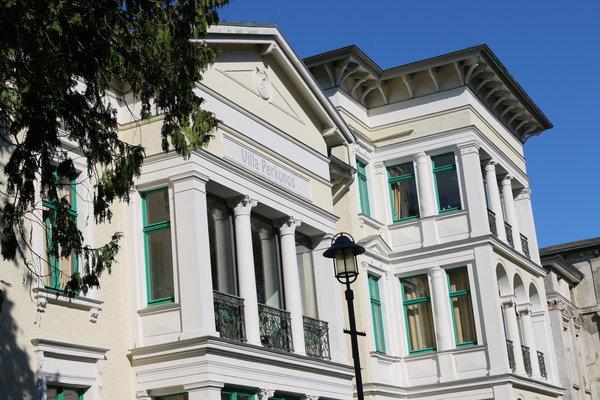 Loggia mit Säulen und großer Glas-Schiebetür im ersten Stock