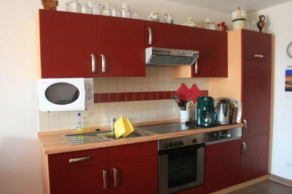 Wohnraum mit kompletter Küchenzeile, bestehend aus Kühlschrank, Herd, Mikrowelle, Spülautomat, Gefrierfach