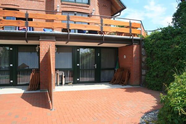 Zugang zur Ferienwohnung mit großer Terrasse und Gartenmöbeln aus Holz und Strandkorb