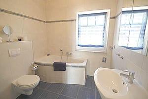 Das Badezimmer mit Badewanne und Dusche