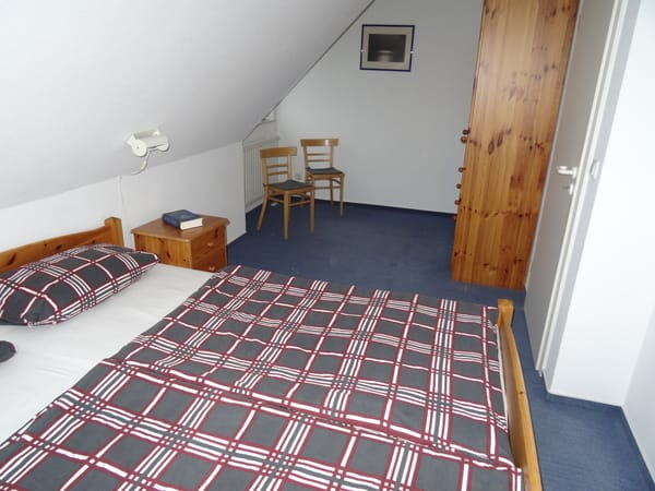 Schlafzimmer mit Doppelbett und Platz für Babybett