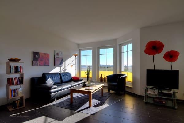 Wohnzimmerecke mit Schlafcouch, großen Erkerfenstern und Blick auf den Zickersee und den Greifswalder Bodden/Ostsee.