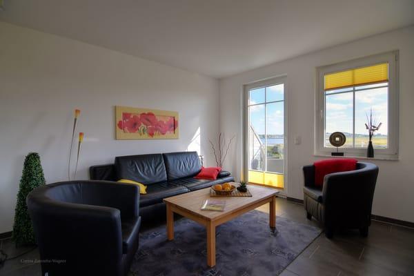 Wohnzimmerecke mit Schlafcouch, Ausgang auf Ihren Balkon u. faszinierende Ausblicke auf den Zickersee, den Greifswalder Bodden und den alten Fischerhafen.