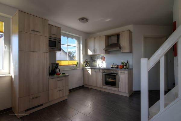 Voll ausgestattete Küche mit Geschirrspülmaschine, großem Gefrierfach u. Kühlschrank, Backofen, Ceranfeld, Microwelle, Kaffeemaschine, Toaster, Wasserkocher und Eierkocher.