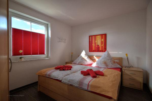 Schlafzimmer mit Doppelbett und großem Kleiderschrank. Die Erstausstattung mit Bettwäsche ist inklusive.