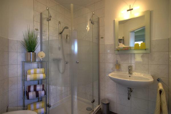 Ihr Badezimmer ist mit einer Dusche ausgestattet. Die Erstausstattung mit Handtüchern und Badetüchern ist inklusive.