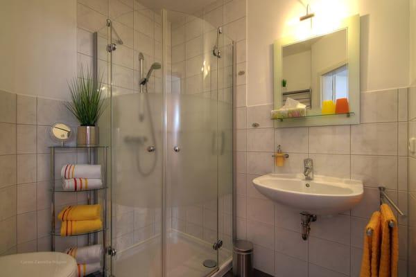 Badezimmer mit Dusche. Die Erstausstattung mit Handtücher und Badetücher ist inklusive.