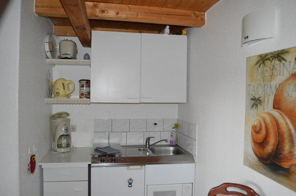 Ein Blick in die Küche mit Esstisch, Kühlschrank, Herd und Mikrowelle. Die Küche ist mit Kaffeemaschine, Wasserkocher und Toaster ausgestattet