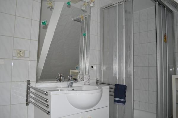 Ein Blick in das Bad mit Waschtisch und Dusche