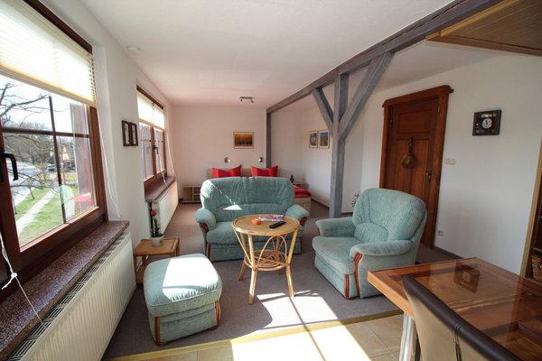 großzügiges Wohnzimmer mit Blick auf die Sitzecke und dem dahinter gelegenen Schlafbereich mit modernem Doppelbett