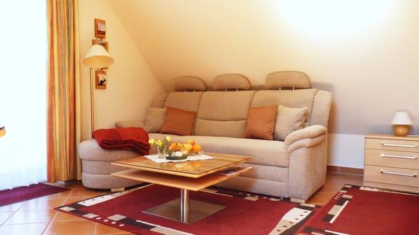 """Couchecke mit Tisch und Standleuchte (ggf. ausklappbar zur Doppelbettliege bei Aufbettung) im Wohnbereich für den gemütlichen Teil des Abends oder bei """"Schietwetter"""""""