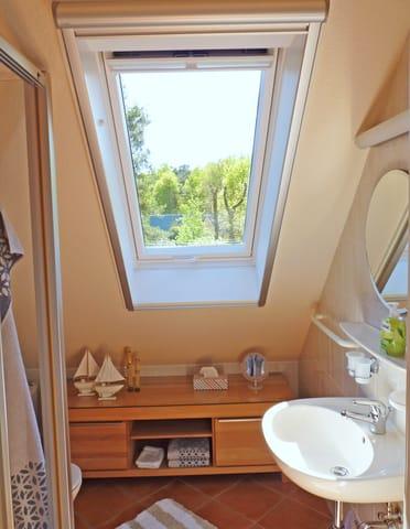 Duschbad, gefliest inkl. Fußboden und Wandheizung, ausgestattet mit Waschtisch, Ablage und Spiegel, WC und Dusche, komplettiert mit ensprechendem Badaccessoires