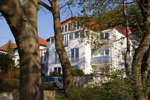 Die Außenansicht im Frühjahr. Die Bäume rings um das Haus zeigen den Anfang des Nationalparks. Vor dem Haus, unten im Bild, trennt ein kleiner Park die Johannis-Kirch-Straße von der unteren Altstadt.