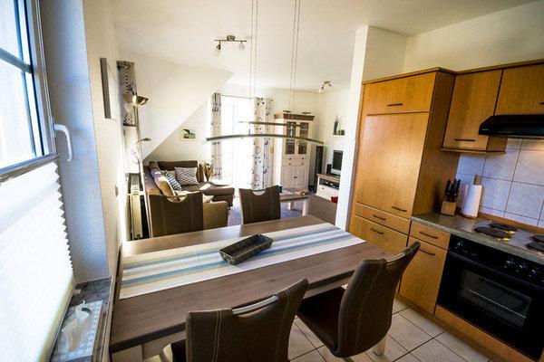 Esstisch mit Küchenzeile und Wohnraum im Hintergrund