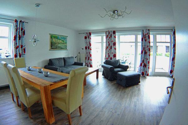 Wohnzimmer mit Esstisch, Schlafcouch und Sessel