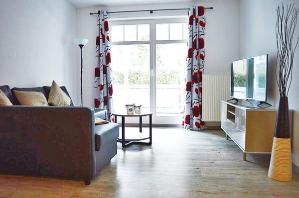 Wohnzimmer mit Flachbild-TV und Schlafcouch