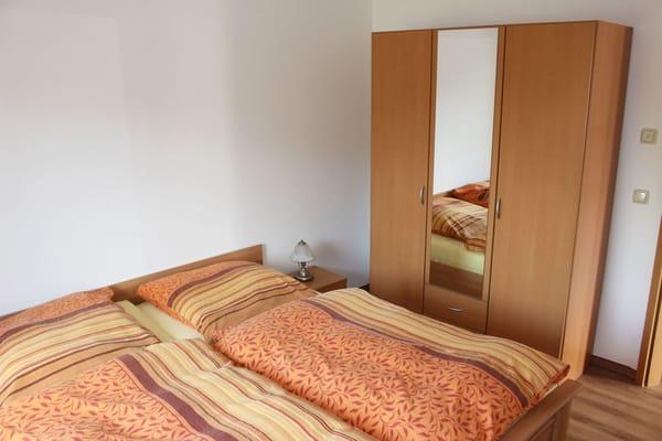 Das Elternschlafzimmer verfügt über ein großes Doppelbett und einen Kleiderschrank.