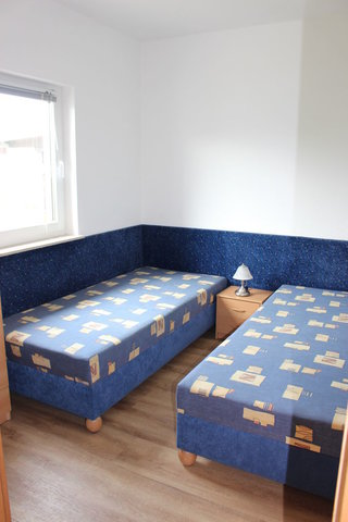 Im zweiten Schlafzimmer befinden sich zwei separate Liegen und ein Kleiderschrank.