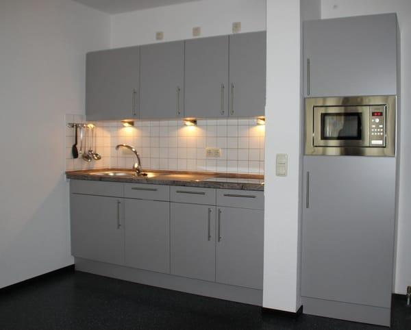 Moderne Küche mit Ceranherd, Geschirrspüler, Kühlschrank und Mikrowelle